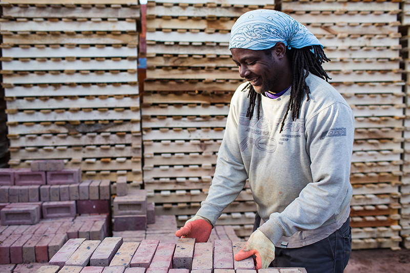Happy worker at HG Matthews hand blending the bricks after the removal from the kiln