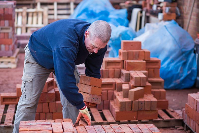 Man at HG Matthews hand blending bricks after firing at the yard
