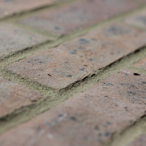 Grey Brown machine made brick, shot along the brick to show texture