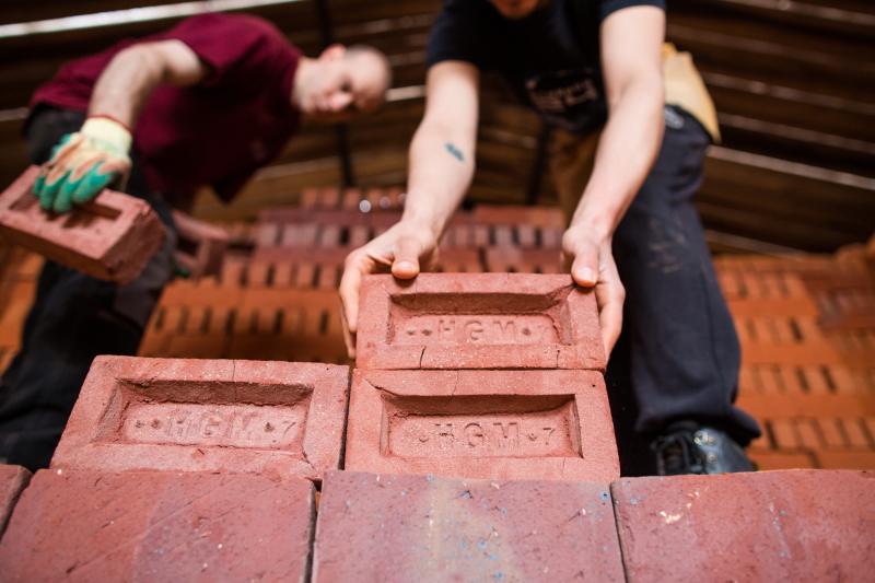 Men carefully removing the bricks from the kiln after firing