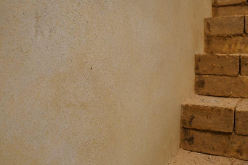 Clay one coat plaster on the wall to the office at HG Matthews with earth block steps leading up to it.