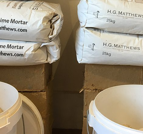 Bags and buckets of HG Matthews Hydraulic Mortar