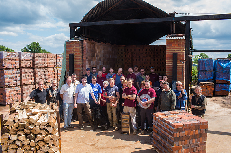 Photo of the team at HG Matthews taken in the yard in front of the woodfire kiln