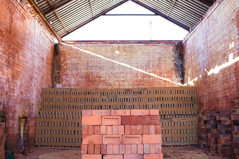 Stack of bricks in a sunlit kiln
