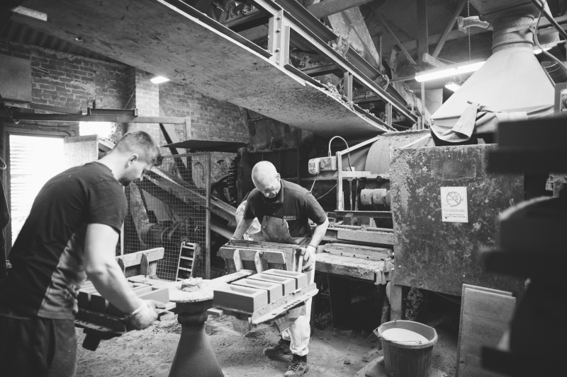 Two men removing machine made bricks in moulds from the machine