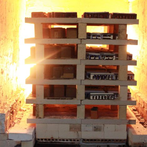 Glazed bricks stacked on shelves in the lit kiln