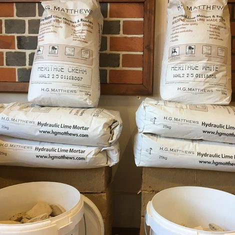 Stacked bags and buckets of HG Matthews Lime Mortars and Renders Range